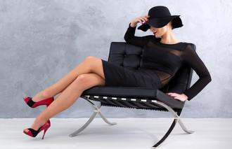 Woman in little black dress sitting in a chair