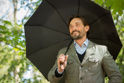 Man with layered jacket smiling while holding umbrella, ralph lauren look, classic style