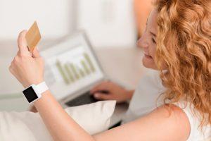 Woman using credit card looking at computer, hiring an interior designer