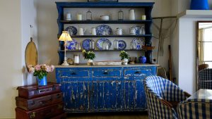 A distressed blue cabinet with antiques and kitchen chair, history of interior design, Michael Gainey Signature Designs