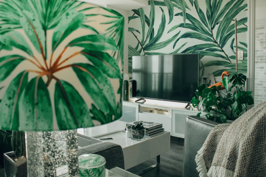 Living room with green plant wallpaper and accents; interior design trends 2019