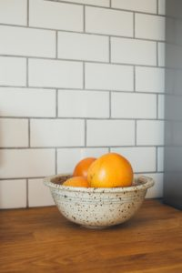 A bowl of oranges in front of a tiled wall; glass backsplash, Michael Gainey Signature Designs