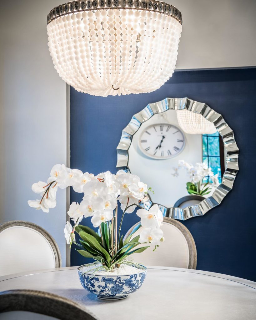 Dining room with blue accent wall and chandelier, Panatone color of the year 2020, Michael Gainey Signature Designs