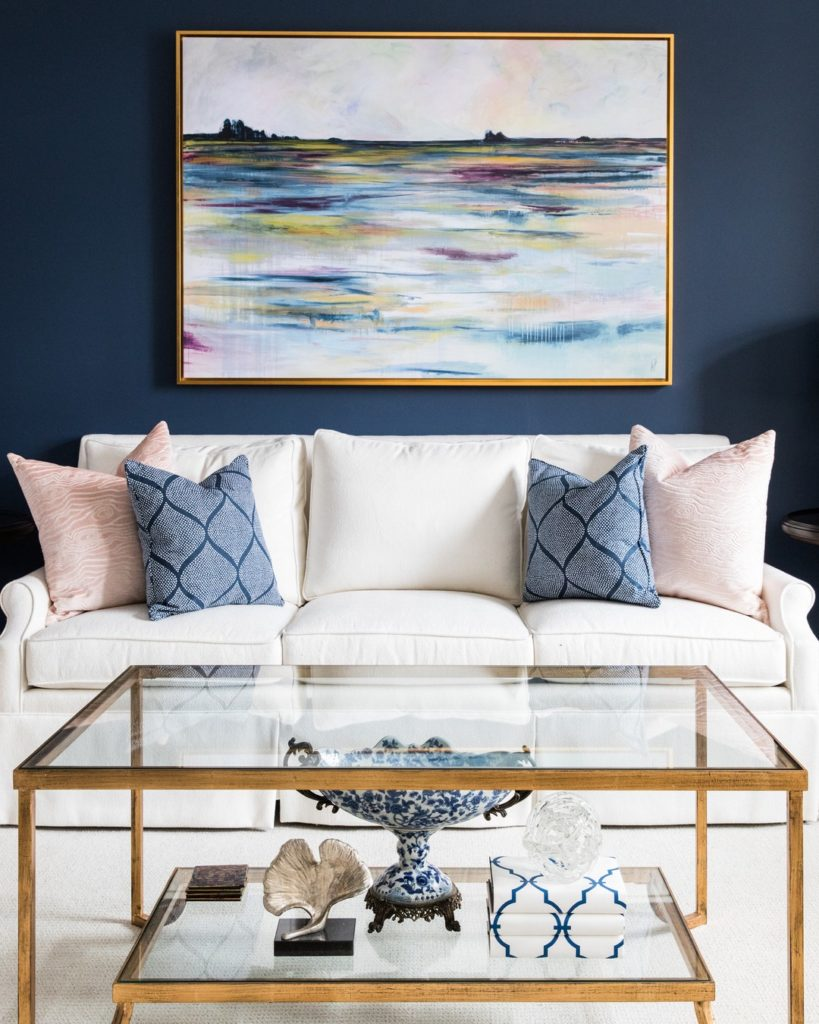 Couch in living room with dark blue wall and artwork, Panatone color of the year 2020, Michael Gainey Signature Designs