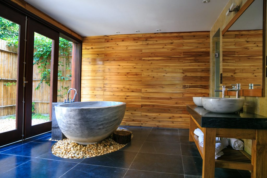 Calming bathroom with wood accent wall and pebble base for the soaking tub, interior design Japandi style, MGSD