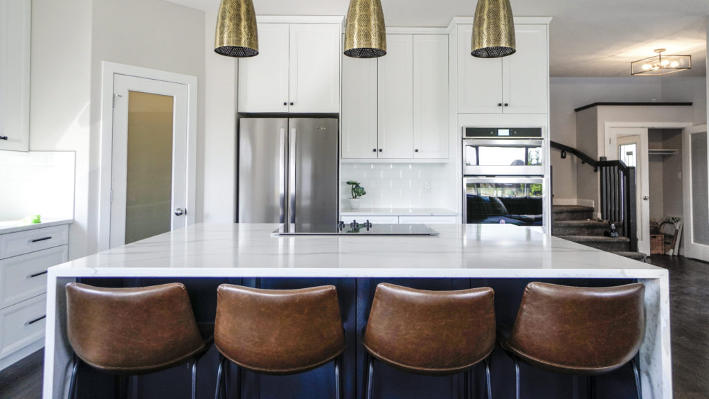 Kitchen with white countertops and island with bar stools; MGSD