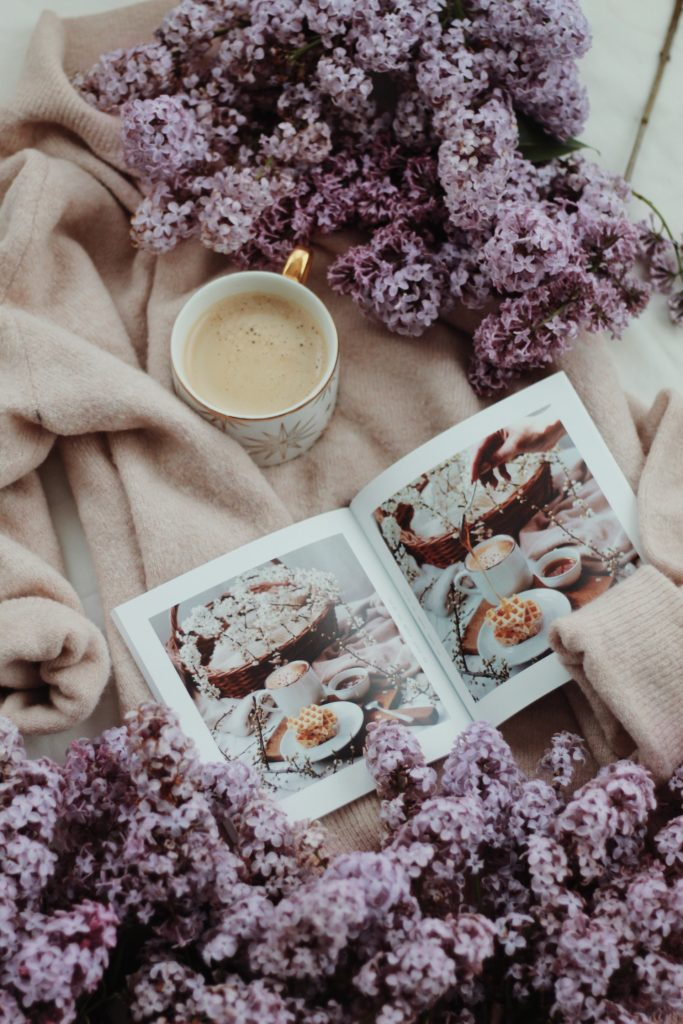Lifestyle photo with purple flowers, magazine, and coffee; MGSD interior decorating tips