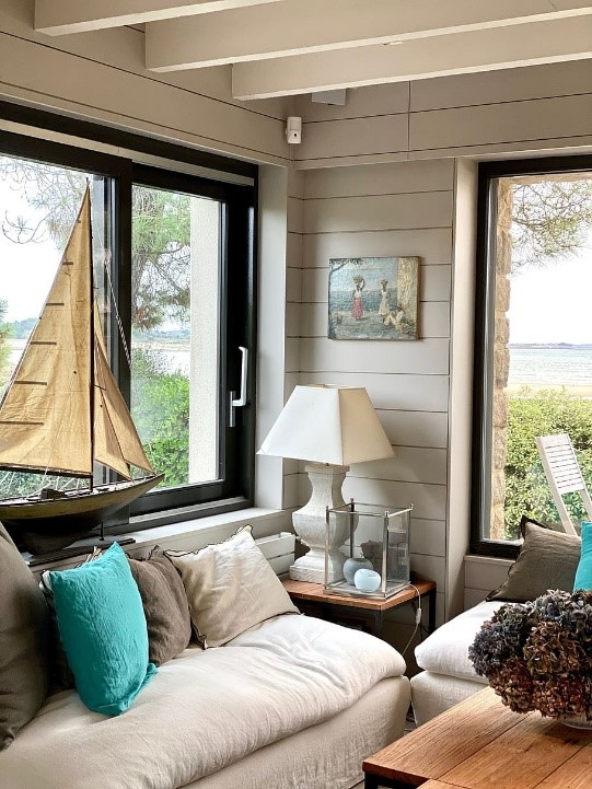 Coastal living room with shiplap and neutral colors; coastal interior design Brevard